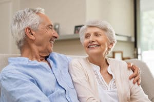 Romantic senior couple laughing while sitting on sofa. Elderly married couple smiling on sofa at home looking at each other. Happy old husband hugging his beautiful wife at home.